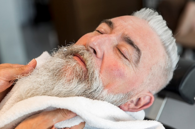 Mit handtuch auf bart des gealterten mannes im friseursalon Kostenlose Fotos