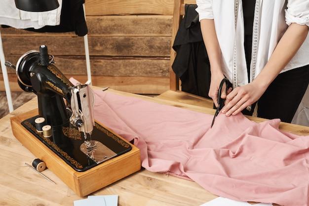Mit mühe wird es passieren. beschnittener schuss von weiblichem schneider, der stoff schneidet, während er an neuer kleidungslinie für ihr geschäft in werkstatt arbeitet, mit nähmaschine und schere während der arbeit. Kostenlose Fotos