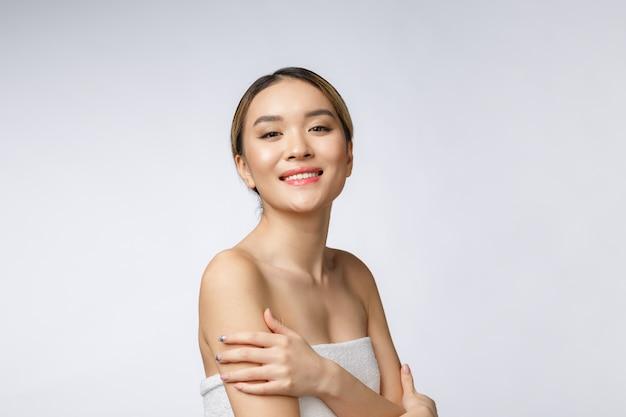 Mit seiten versehenes porträt des asiatischen schönen lächelnden mädchens mit dem kurzen haar, das ihre gesunde haut zeigt Premium Fotos