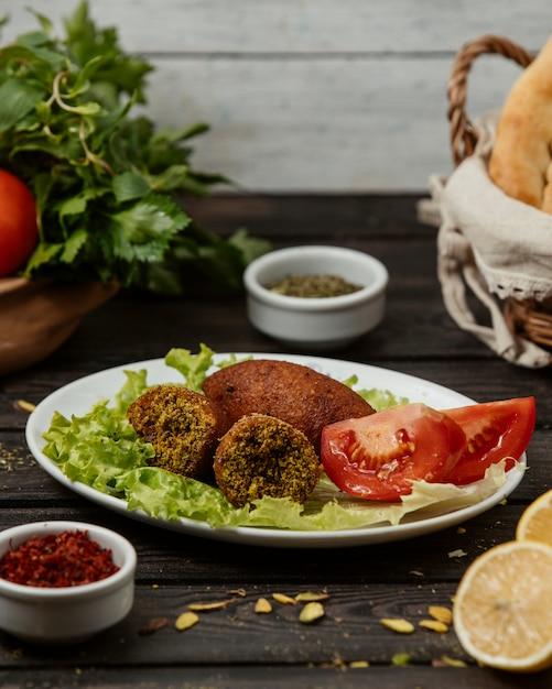Mit türkischem kibbeh gefüllte fleischbällchen, serviert mit tomaten und salat Kostenlose Fotos