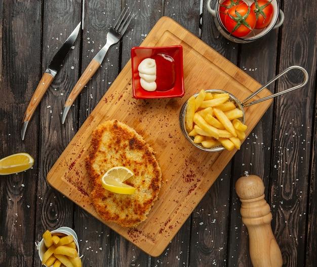 Mit zitrone garnierte hähnchenbrustpastetchen, serviert mit pommes frites, mayonnaise und ketchup Kostenlose Fotos