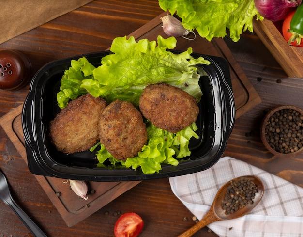 Mitnehmer des rindfleischkoteletts diente mit kopfsalat im schwarzen behälter. Kostenlose Fotos