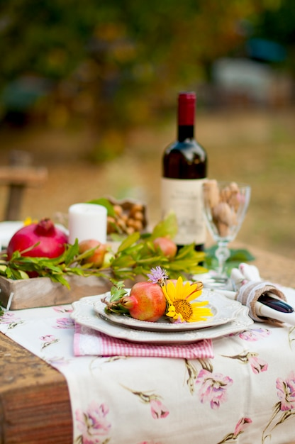 Mittagessen im garten mit wein und obst. romantisches abendessen im freien. herbstlaub von blumen. wunderschönes tisch-scrapbooking. Premium Fotos