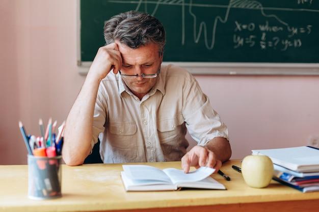 Mittelalterlehrer in den gläsern lehrbuch im klassenzimmer aufmerksam lesend. Premium Fotos