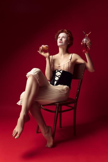 Mittelalterliche rothaarige junge frau als herzogin im schwarzen korsett und in der nachtwäsche, die auf einem stuhl auf rotem raum mit einem getränk und donut sitzt Kostenlose Fotos