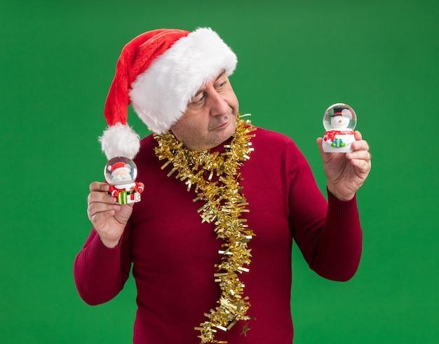 Mittelalterlicher mann, der weihnachtsweihnachtsmütze mit lametta um den hals hält, der weihnachtsschneekugeln hält, die verwirrt schauen, die zweifel haben, über grünem hintergrund stehen Kostenlose Fotos