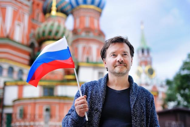 Mittelaltermann, der russische flagge mit der kathedrale des heiligen basilikums hält Premium Fotos
