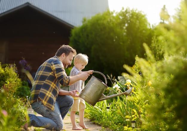 Mittelaltermann und sein kleiner sohn, die blumen im garten am sonnigen tag des sommers wässern Premium Fotos