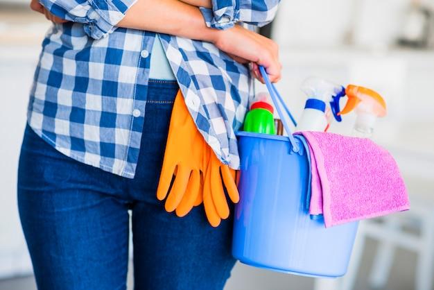 Mittelteil der hand der frau, die reinigungsausrüstungen im eimer hält Kostenlose Fotos