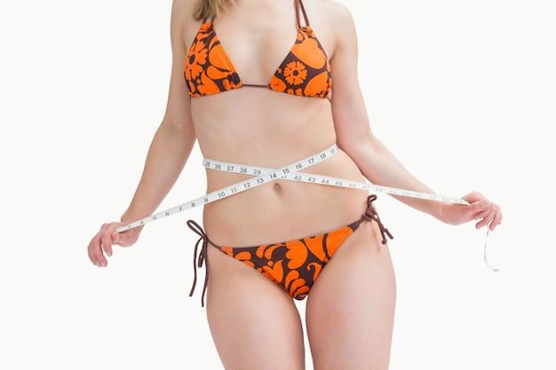 Mittelteil der jungen frau in messender taille des bikinis Premium Fotos