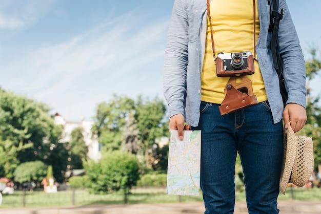 Mittelteil der tragenden kamera des touristischen mannes und des haltens der karte und des hutes am park Kostenlose Fotos