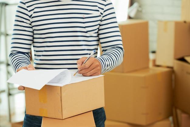 Mittelteil des mannes in gestreiftem langarmhemd, der das formular auf dem karton ausfüllt Kostenlose Fotos