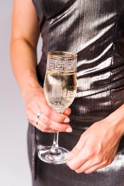 Mittelteil des weiblichen haltenen champagnerglases Kostenlose Fotos