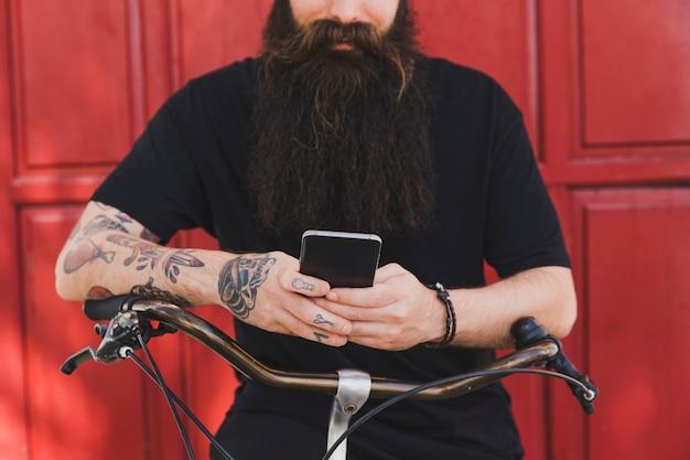 Mittelteil eines mannes, der auf fahrrad gegen rote tür unter verwendung des handys sitzt Kostenlose Fotos