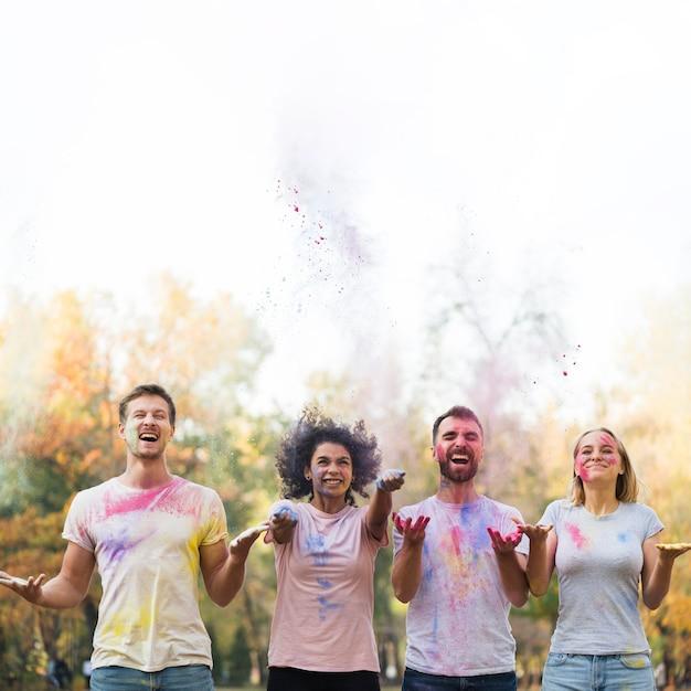 Mittlere einstellung von freunden, die farbe für holi werfen Kostenlose Fotos