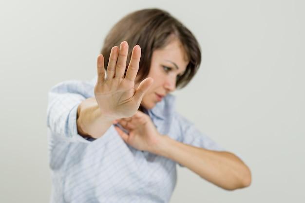Mittlere erwachsene emotionale frau, die stoppschild zeigt. Premium Fotos