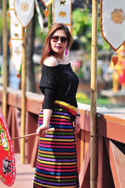 Mittlere gealterte thailändische dame im bunten thailändischen artnordkostüm touristischen platz am im freien in chiang mai lanna thailand Kostenlose Fotos