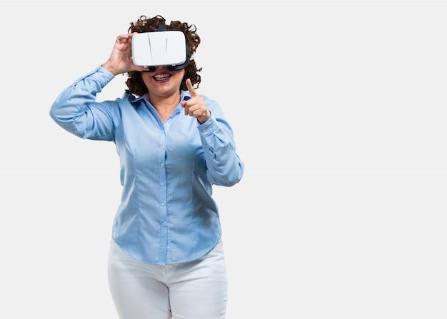 Mittlere greisin aufgeregt und unterhalten, spielend mit gläsern der virtuellen realität Premium Fotos