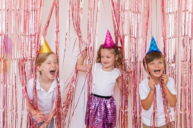 Mittlere schuss glückliche kinder, die partyhüte tragen Kostenlose Fotos