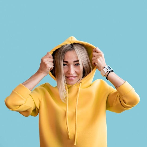 Mittlere schuss smiley asiatische frau, die einen gelben kapuzenpulli trägt Kostenlose Fotos