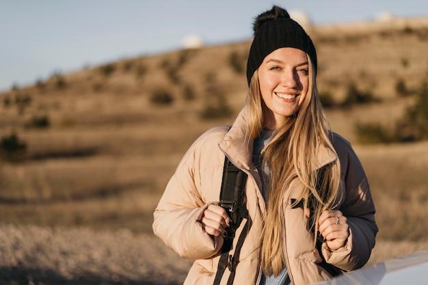 Mittlere schuss smiley-frau mit rucksack Kostenlose Fotos