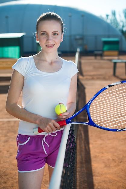 Mittlere schussfrau auf dem tennisfeld Kostenlose Fotos