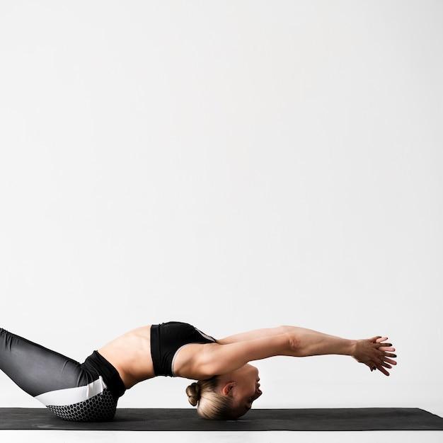 Mittlere schussfrau auf yogamatte Kostenlose Fotos