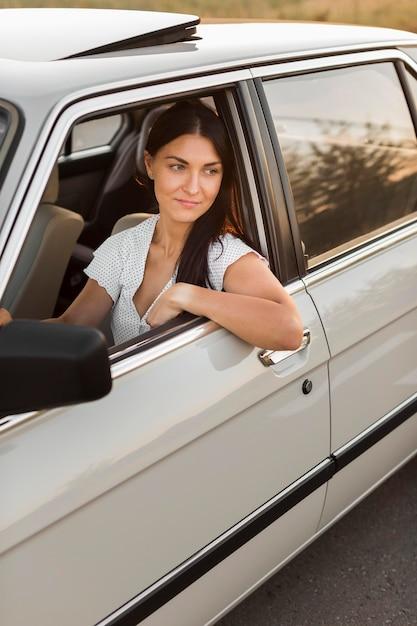 Mittlere schussfrau, die altes auto fährt Kostenlose Fotos