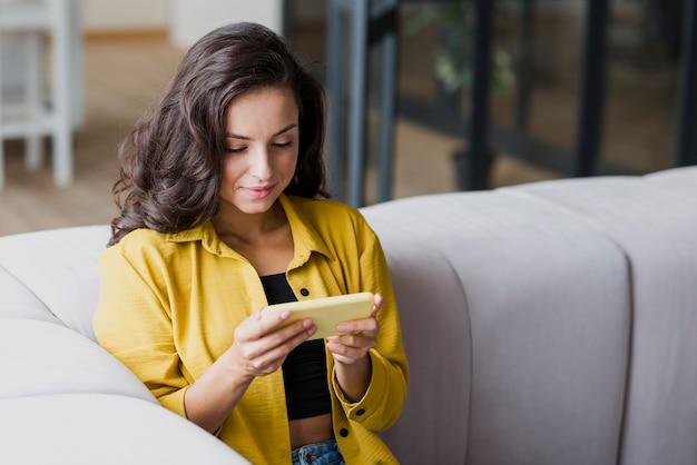 Mittlere schussfrau, die am telefon spielt Kostenlose Fotos