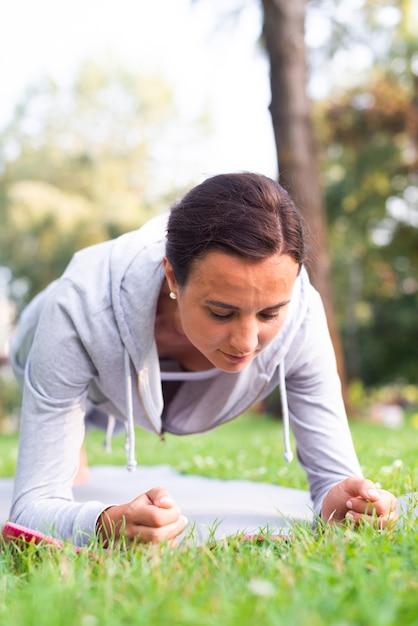 Mittlere schussfrau, die draußen planken tut Kostenlose Fotos