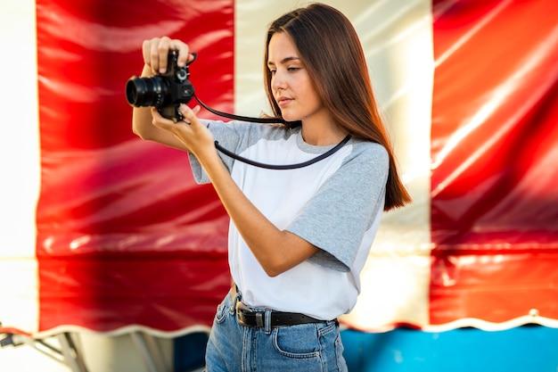 Mittlere schussfrau, die foto mit kamera macht Kostenlose Fotos