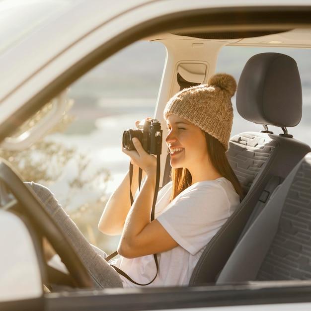 Mittlere schussfrau, die fotokamera hält Kostenlose Fotos