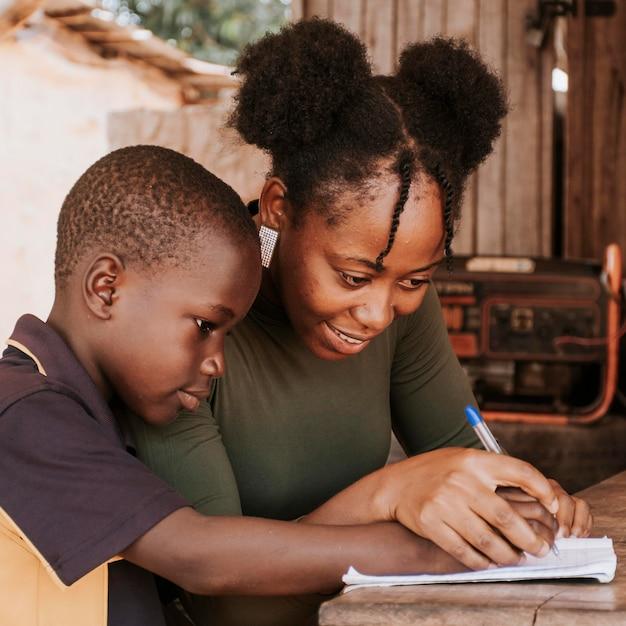 Mittlere schussfrau, die kind lehrt, zu schreiben Kostenlose Fotos