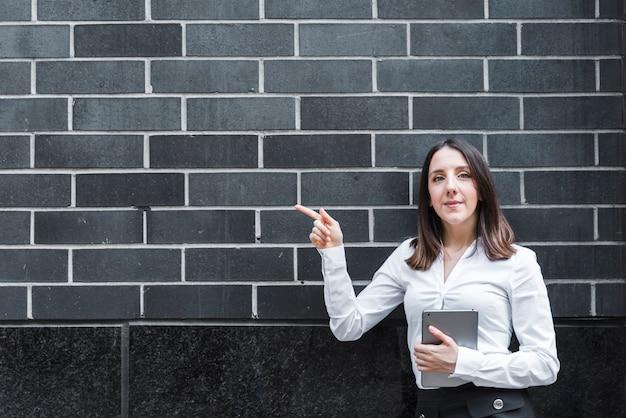 Mittlere schussfrau mit tablette zeigend auf wand Kostenlose Fotos