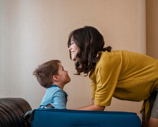 Mittlere schussfrau und kind mit gepäck Kostenlose Fotos