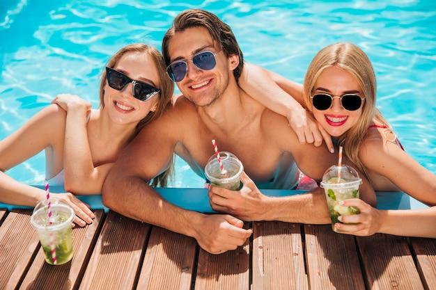 Mittlere schussfreunde, die kamera im swimmingpool betrachten Kostenlose Fotos