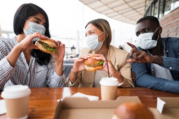 Mittlere schussfreunde, die masken am tisch tragen Kostenlose Fotos