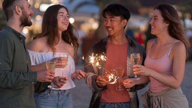 Mittlere schussfreunde, die mit feuerwerk feiern Kostenlose Fotos