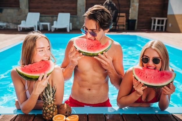 Mittlere schussfreunde, die wassermelone im pool essen Kostenlose Fotos