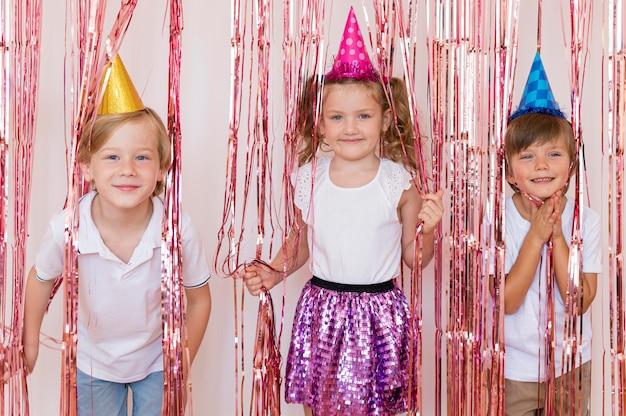 Mittlere schusskinder, die partyhüte tragen Kostenlose Fotos