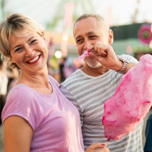 Mittlere schussleute, die zuckerwatte essen Kostenlose Fotos