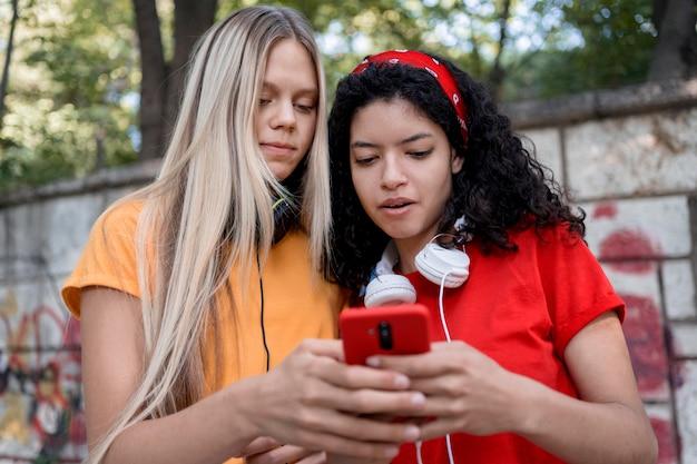 Mittlere schussmädchen, die telefon betrachten Kostenlose Fotos
