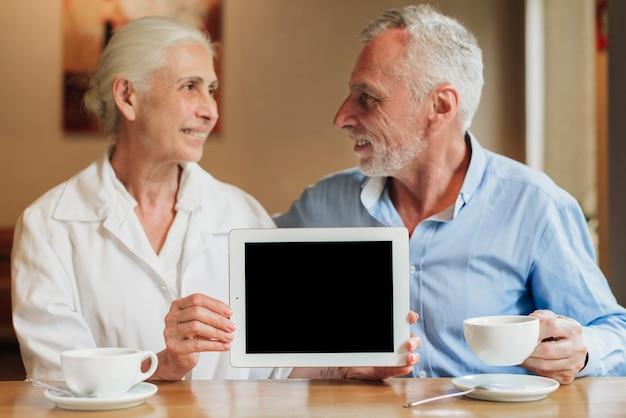 Mittlere schusspaare, die ein tablettenmodell halten Kostenlose Fotos