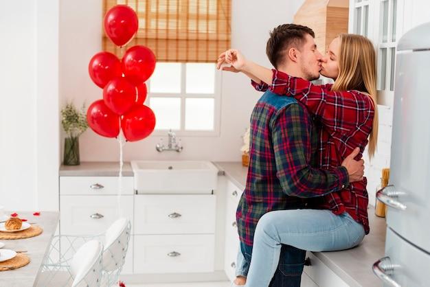 Mittlere schusspaare, die in der küche küssen Kostenlose Fotos