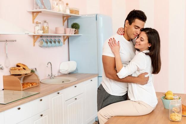 Mittlere schusspaare, die in der küche umarmen Kostenlose Fotos