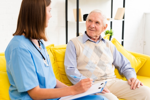Mittlere schusspflegekraft, die mit altem mann spricht Kostenlose Fotos