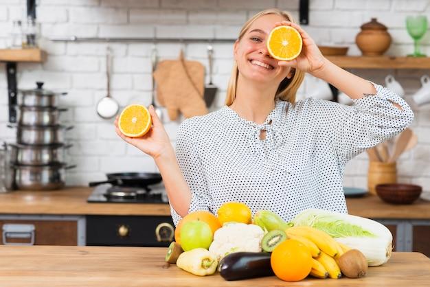 Mittlere schusssmileyfrau, die mit orangen spielt Kostenlose Fotos