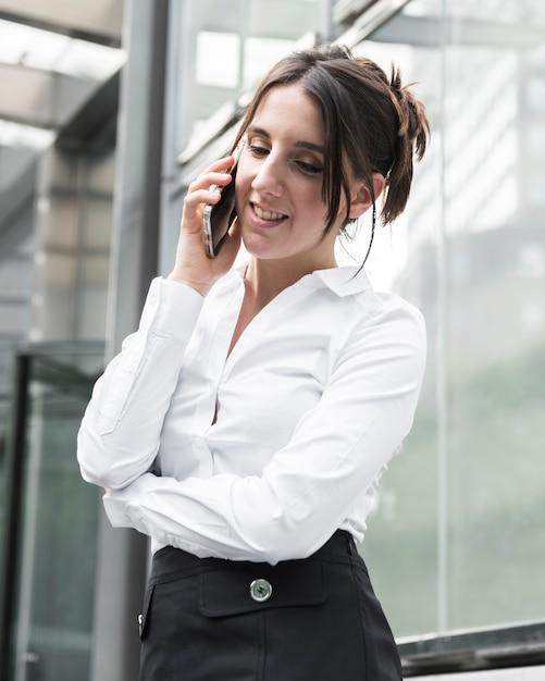 Mittlere schusssmileyfrau, die telefonisch spricht Kostenlose Fotos
