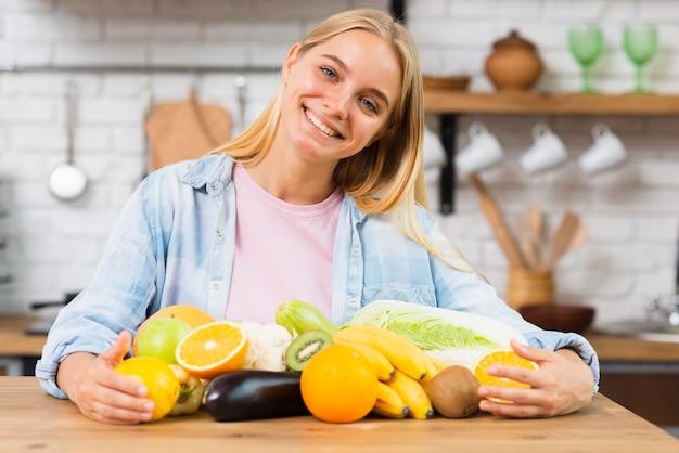 Mittlere schusssmileyfrau mit frucht in der küche Kostenlose Fotos