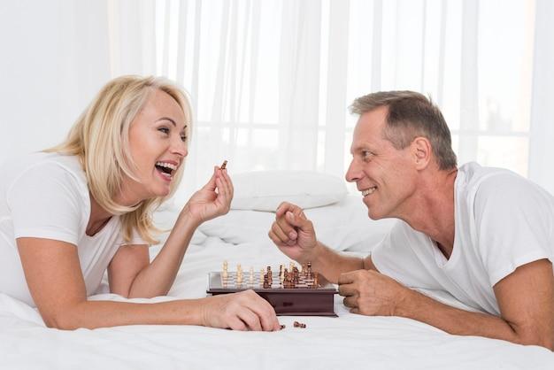 Mittlere schusssmileypaare, die schach im schlafzimmer spielen Kostenlose Fotos